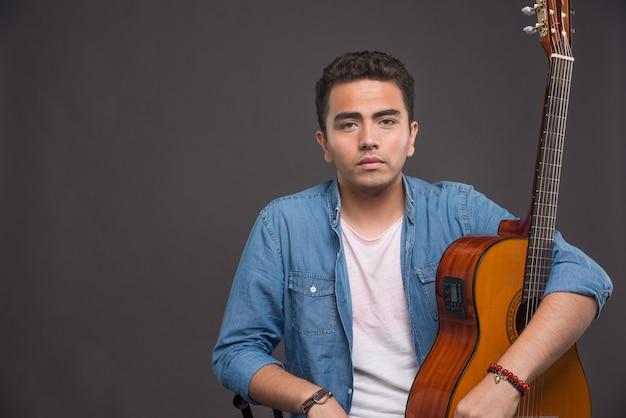 Jeune homme à la guitare à la sérieuse sur fond sombre.