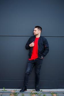 Un jeune homme habillé dans un style décontracté, une veste noire, un jean, un t-shirt rouge. il est contre un mur gris