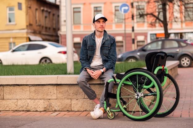 Un jeune homme handicapé est assis sur un banc à côté d'un fauteuil roulant photo de haute qualité