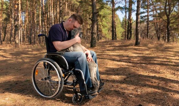Jeune homme handicapé en fauteuil roulant caressant un charmant chien dressé se relaxant ensemble dans la nature