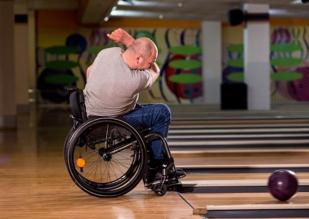 Jeune homme handicapé en fauteuil roulant jouant au bowling dans le club
