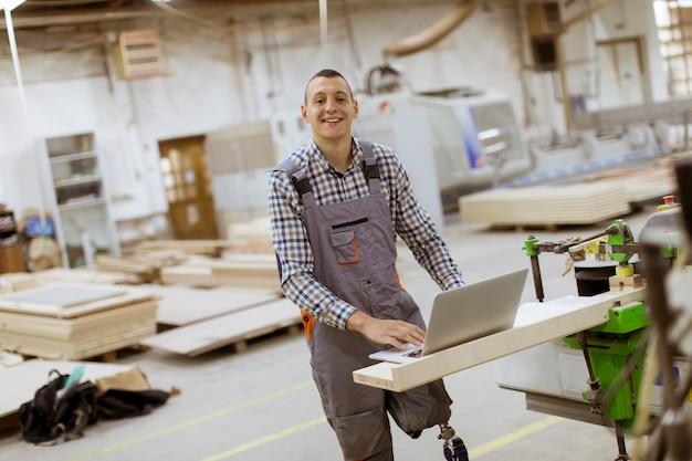 Jeune homme handicapé avec une jambe artificielle travaille à la fabrique de meubles