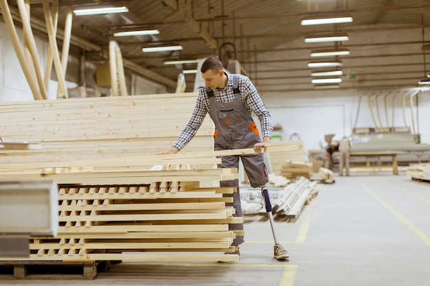 Jeune homme handicapé avec une jambe artificielle travaille à l'usine de meubles