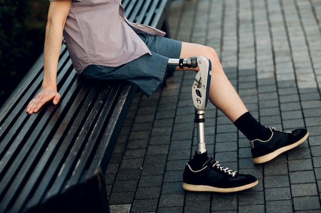 Jeune homme handicapé avec prothèse de pied assis en plein air