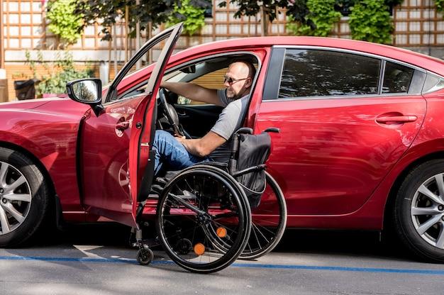Jeune homme handicapé sur le siège du conducteur de sa voiture.