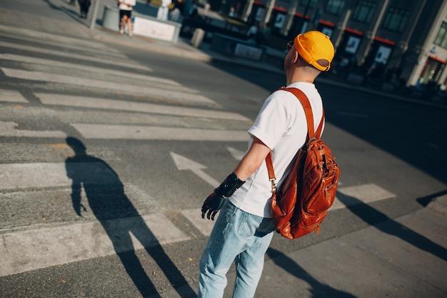 Jeune homme handicapé voyageur avec main prothétique artificielle en vêtements décontractés et sac à dos marchant un ...