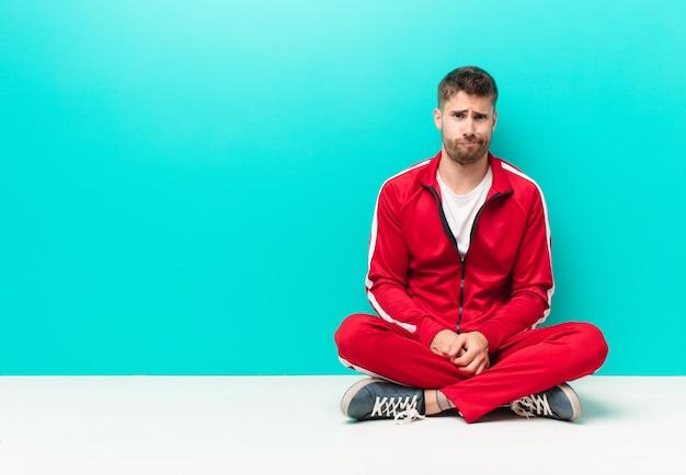Jeune homme handosme se sentant confus et douteux, se demandant ou essayant de choisir ou de prendre une décision contre le mur de couleur plat