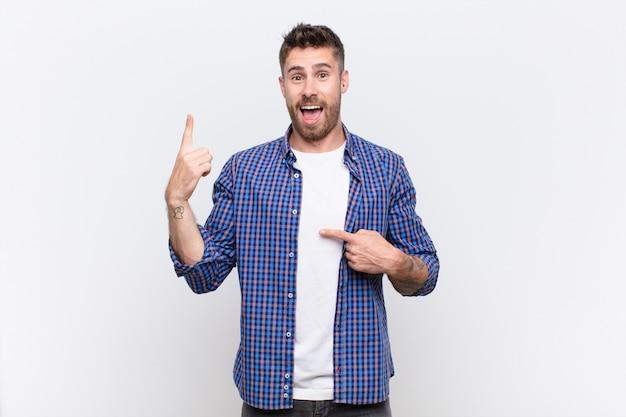Jeune homme handosme se sentant fier et surpris, pointant vers soi avec confiance, se sentant comme numéro un succès contre un mur de couleur plat