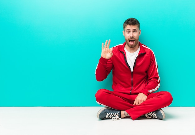 Jeune homme handosme se sentant réussi et satisfait, souriant avec la bouche grande ouverte, faisant signe avec la main contre le mur de couleur plat
