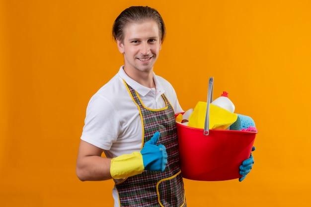 Jeune homme hansdome portant un tablier et des gants en caoutchouc tenant un seau avec des outils de nettoyage