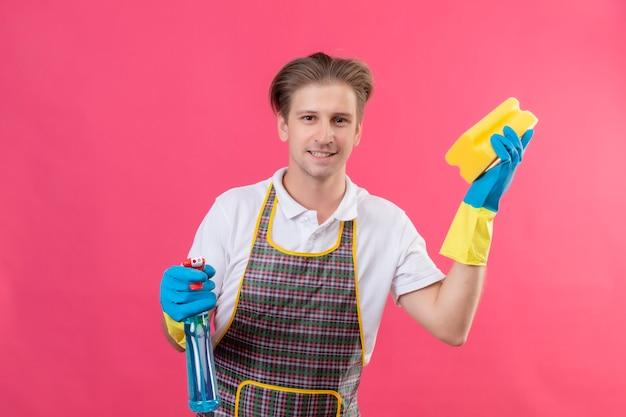 Jeune homme hansdome portant un tablier et des gants en caoutchouc tenant un spray de nettoyage et une éponge avec un sourire confiant prêt à cean debout sur un mur rose 2