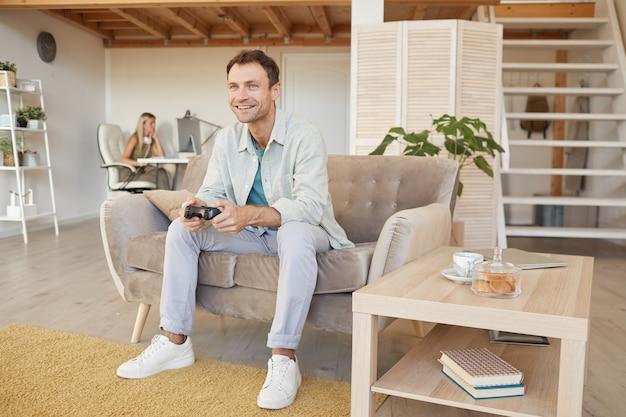 Jeune homme heureux assis sur un canapé et jouer à des jeux informatiques pendant son temps libre à la maison
