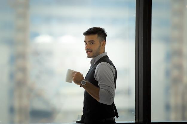 Un jeune homme heureux boit du café et sourit en se tenant debout au café