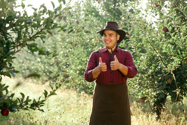 Jeune homme heureux dans le jardin la collecte de pommes mûres