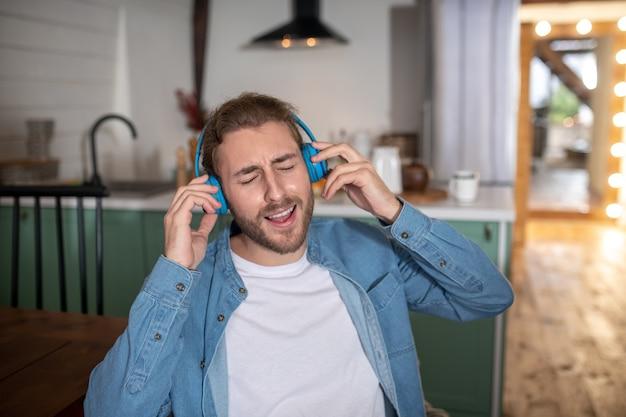 Un jeune homme heureux écoutant sa chanson préférée