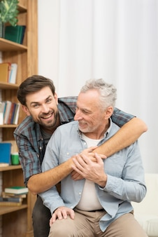 Jeune homme heureux embrassant un homme âgé