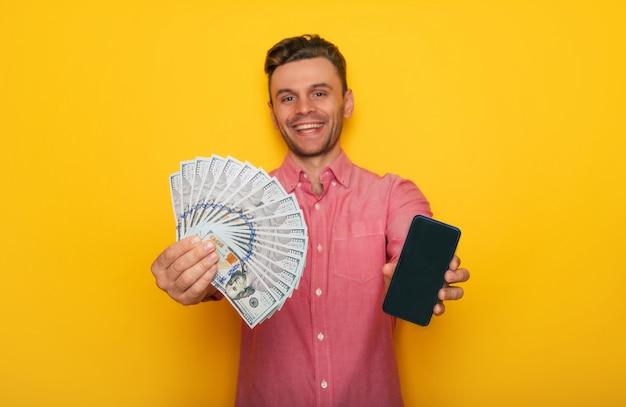 Un jeune homme heureux et excité détient une carte de crédit et beaucoup d'argent dans les mains sur fond jaune