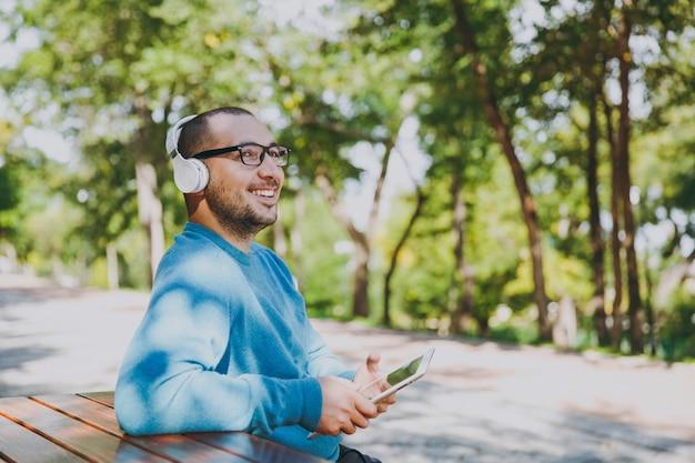 Jeune homme heureux, homme d'affaires ou étudiant dans des lunettes de chemise bleue décontractée, assis à table avec un casque, une tablette dans le parc de la ville, écouter de la musique, se reposer à l'extérieur sur la nature verdoyante. concept de loisirs de style de vie.