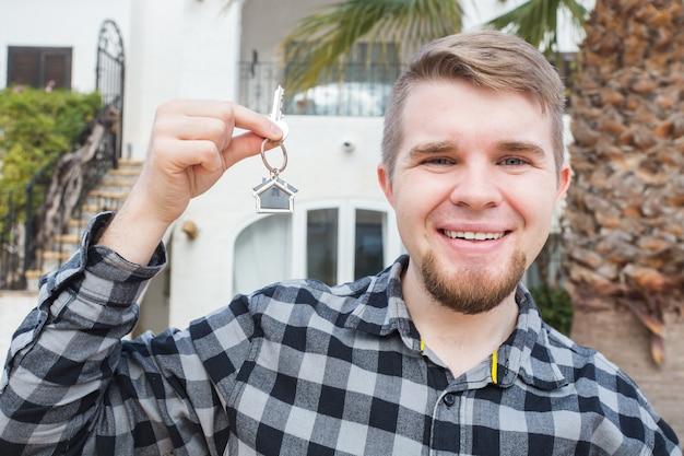 Jeune homme heureux montrant une clé de la maison