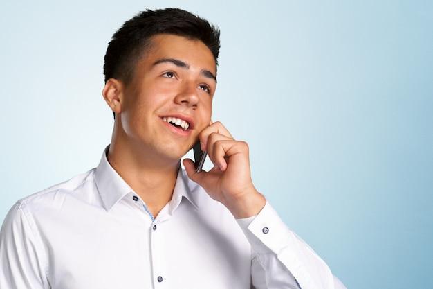 Jeune homme heureux occasionnel au téléphone