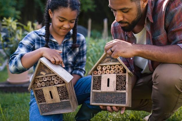 Un jeune homme heureux avec une petite soeur tenant des hôtels à insectes à l'extérieur dans la cour.