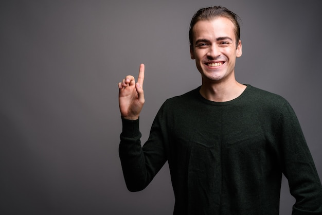 Jeune homme heureux pointant le doigt vers le haut et montrant l'espace de copie