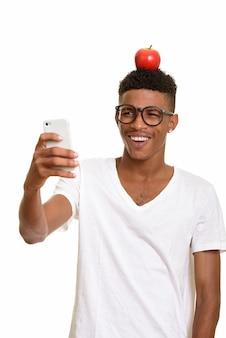 Jeune homme heureux avec pomme sur la tête tout en prenant selfie