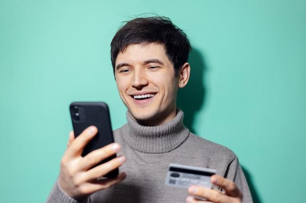 Jeune homme heureux avec smartphone et carte de crédit à la main sur le mur de couleur aqua menthe.