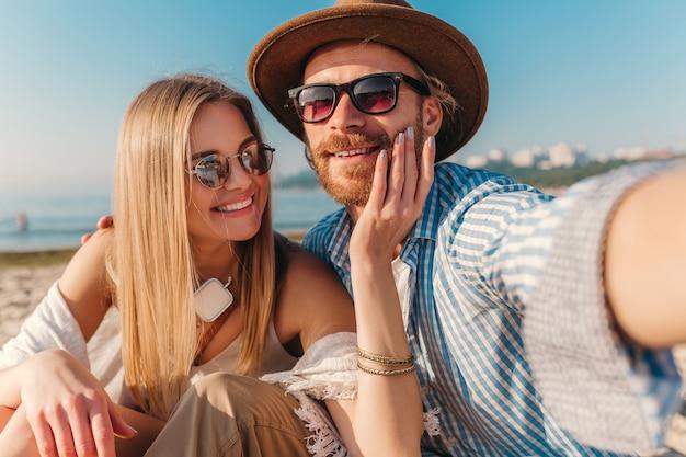 Jeune homme heureux souriant attrayant et femme à lunettes de soleil assis sur la plage de sable prenant selfie photo