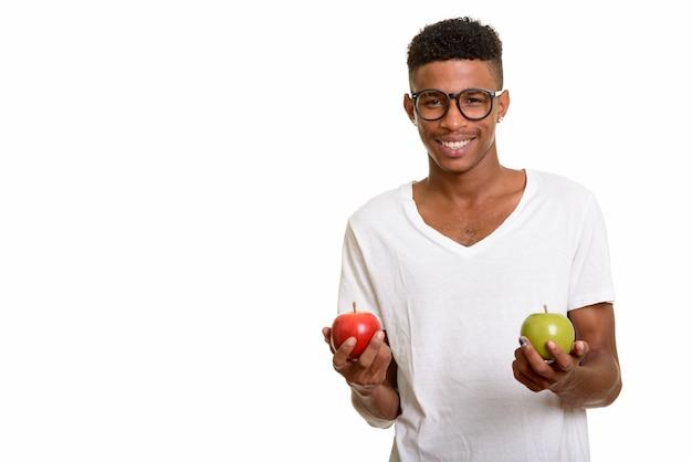 Jeune homme heureux tenant une pomme rouge et verte