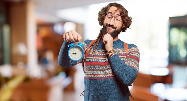Jeune homme hippie avec une horloge d'alarme
