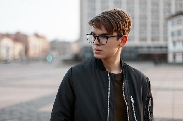 Jeune homme hipster américain dans des lunettes élégantes avec une coiffure à la mode dans des vêtements élégants dans la rue de la ville. mec attrayant.