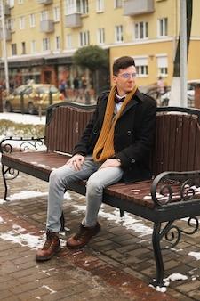 Jeune homme hipster assis sur un banc, regarde ailleurs, en hiver dehors