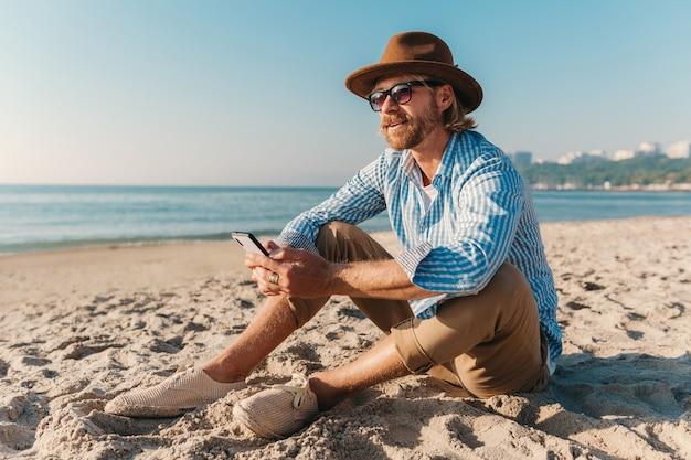 Jeune homme hipster attrayant assis sur la plage au bord de la mer en vacances d'été