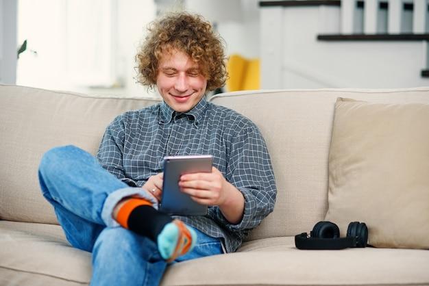 Jeune homme hipster aux cheveux bouclés assis sur le canapé et tenant la tablette dans les mains