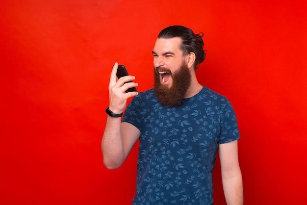 Jeune homme hipster barbu criant au smartphone sur fond rouge