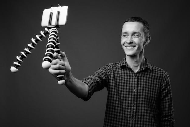 Jeune homme hipster contre mur gris en noir et blanc