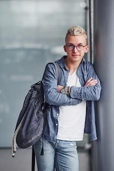 Jeune homme hipster dans de beaux vêtements se tient à l'intérieur