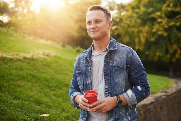 Jeune homme hipster debout avec du café à emporter dans le parc, souriant agréablement à la caméra. heureux beau mec sans soucis en veste en jean bleu