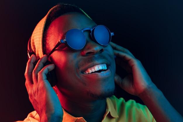Jeune homme hipster écoute de la musique avec des écouteurs au studio noir avec néons.