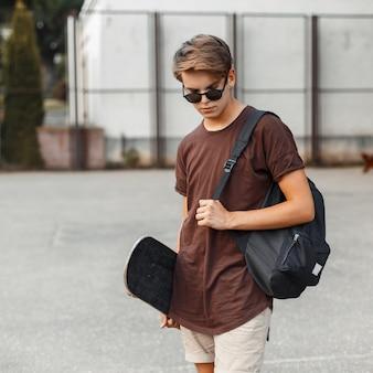 Jeune homme hipster élégant dans des lunettes de soleil à la mode dans un t-shirt élégant en short à la mode avec un sac à dos de sport avec une planche à roulettes se dresse sur un terrain de basket par une chaude journée d'été