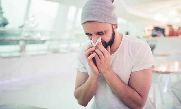 Jeune homme hipster éternue dans une serviette blanche. malade et malade. maladie du coronavirus. restez seul et nettoyez-vous. à l'intérieur d'un bâtiment, d'un café ou d'un restaurant, peut-être d'un bureau