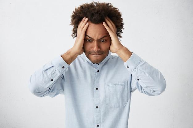 Jeune homme hipster à la peau sombre portant une chemise blanche tenant les mains sur la tête à désespérément vers le bas