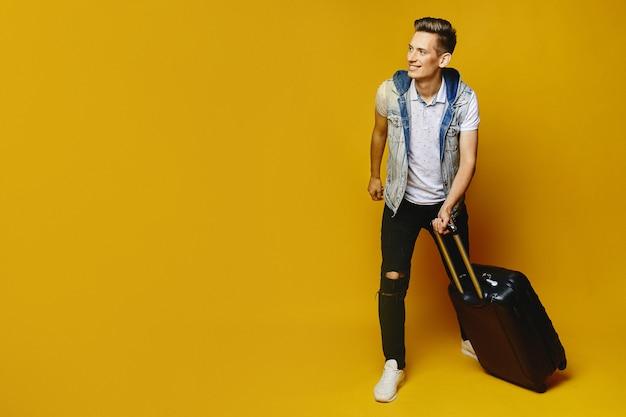 Jeune homme hipster en tenue décontractée marche avec des valises