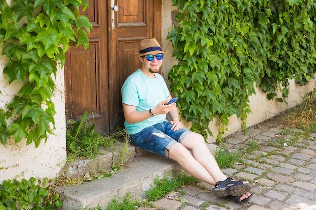 Jeune homme hipster utilisant un téléphone intelligent mobile à l'extérieur