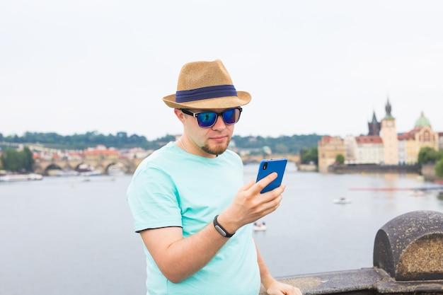Jeune homme hipster utilisant un téléphone intelligent mobile en plein air