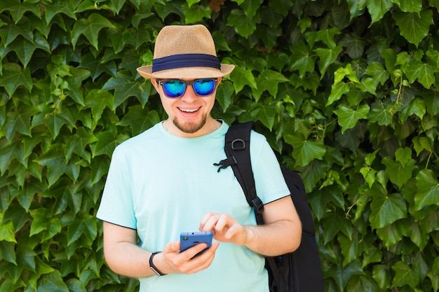 Jeune homme hipster utilisant un téléphone intelligent mobile.