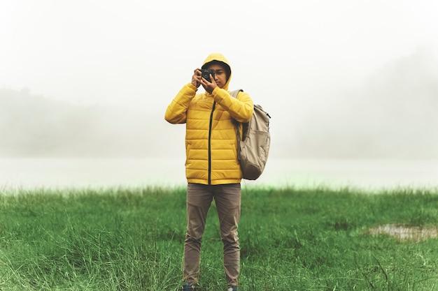 Jeune homme hipster avec une veste lumineuse prenant une photo d'un paysage incroyable sur fond brumeux vintage