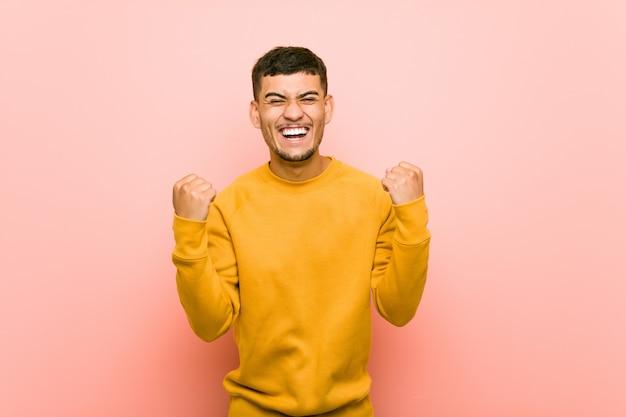 Jeune homme hispanique acclamant insouciant et excité. la victoire .