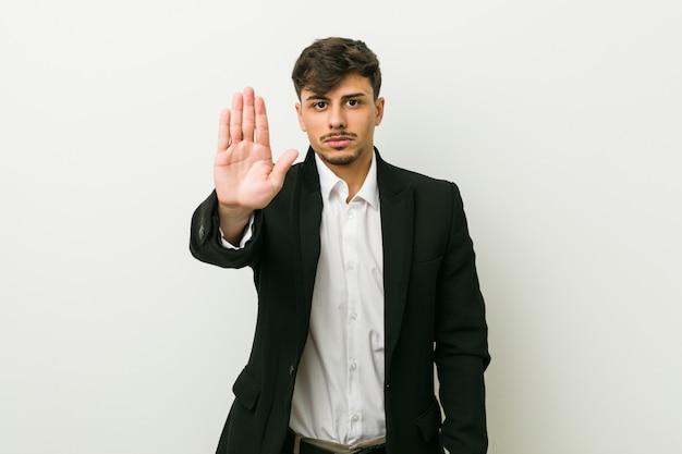 Jeune homme hispanique d'affaires debout avec la main tendue montrant le panneau d'arrêt, vous empêchant.